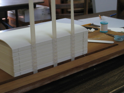 A stack of sewn books on the frame small